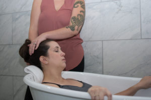 Pregnant person in tub, doula helping to relax client